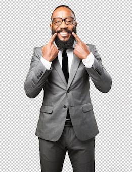 Uomo di colore di affari che indica la sua bocca