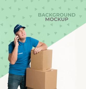 Uomo di consegna che parla al telefono con un cliente con mock-up di sfondo