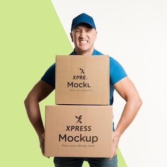 Uomo di consegna che tiene alcune scatole mock-up