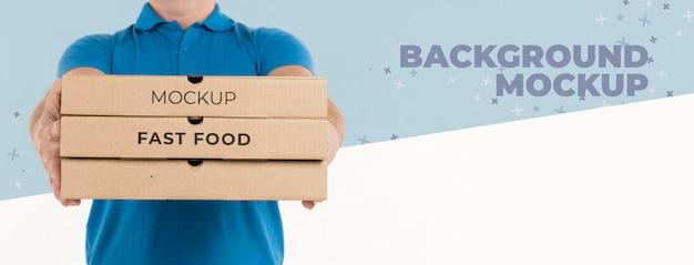 Uomo di consegna che tiene scatole per pizza