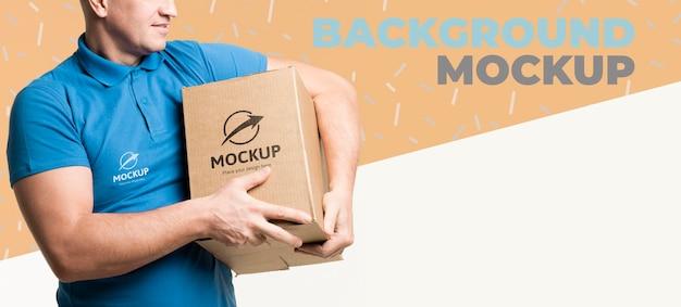 Uomo di consegna che tiene un mock-up di scatola