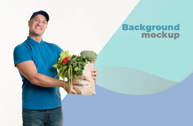 Uomo di consegna che tiene un sacchetto di generi alimentari