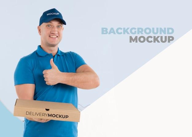 Uomo di consegna che tiene una scatola con pizza