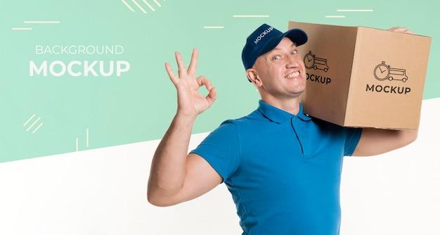 Uomo di consegna di smiley che tiene una scatola