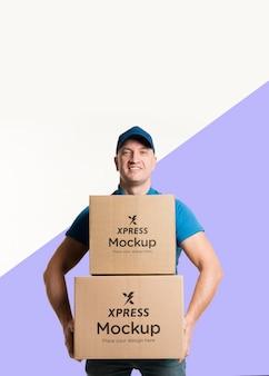 Uomo di consegna di vista frontale che tiene alcune scatole mock-up