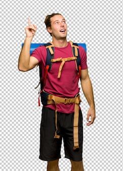 Uomo di escursionista con zaino in spalla di montagna che intende realizzare la soluzione sollevando un dito