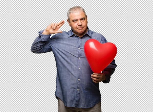 Uomo di mezza età che celebra san valentino facendo un gesto di suicidio