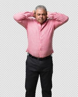 Uomo di mezza età che copre le orecchie con le mani, arrabbiato e stanco di sentire un po 'di suono