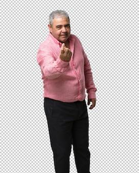 Uomo di mezza età che invita a venire, fiducioso e sorridente a fare un gesto con la mano, essere positivo e amichevole