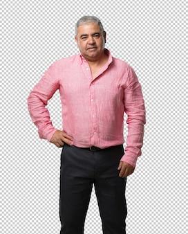 Uomo di mezza età con le mani sui fianchi, in piedi, rilassato e sorridente, molto positivo e allegro
