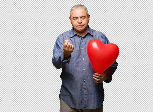 Uomo di mezza età festeggia il giorno di san valentino facendo un gesto di necessità