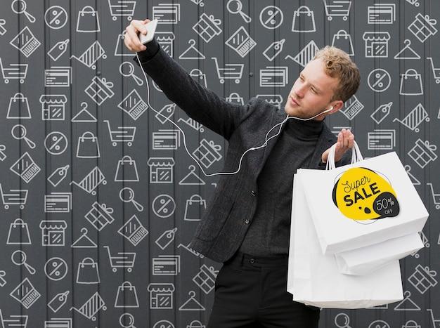 Uomo di smiley che prende selfie con i suoi acquisti