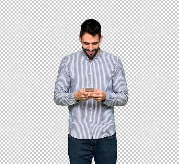 Uomo elegante con la camicia che invia un messaggio con il cellulare