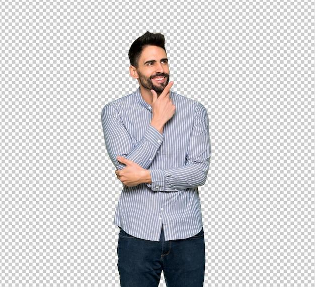 Uomo elegante con la camicia che pensa un'idea mentre osserva in su