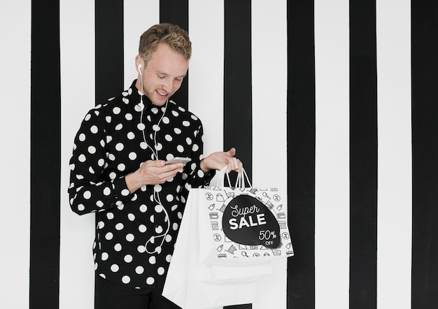 Uomo felice con i sacchetti della spesa che esamina cellulare