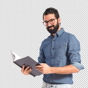 Uomo felice dei pantaloni a vita bassa che legge un libro
