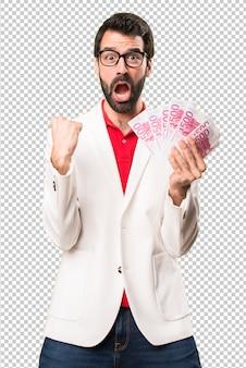Uomo felice del brunette con gli occhiali che prendono molti soldi