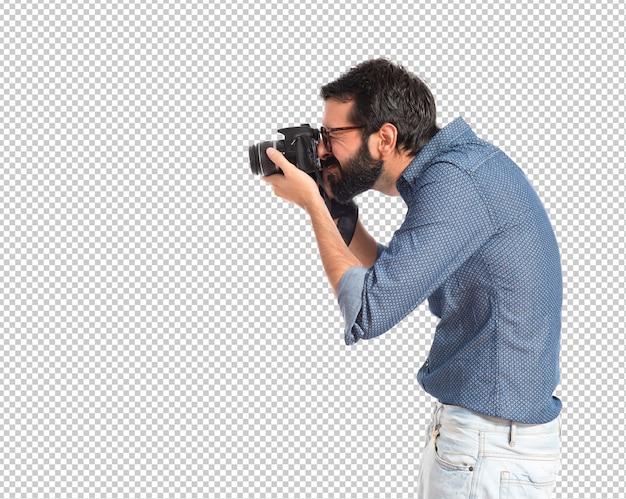 Uomo giovane hipster fotografando su sfondo bianco