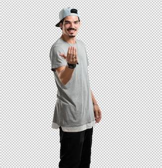 Uomo giovane rapper che invita a venire, fiducioso e sorridente facendo un gesto con la mano, essendo positivo e amichevole