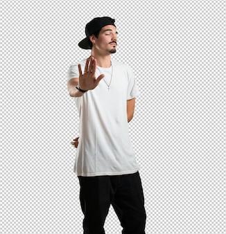 Uomo giovane rapper serio e determinato, mettendo la mano davanti, ferma gesto