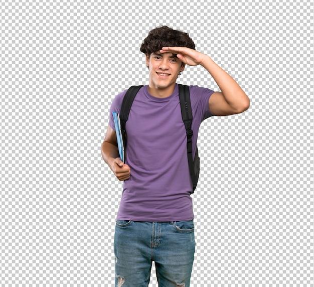 Uomo giovane studente che guarda lontano con la mano per guardare qualcosa