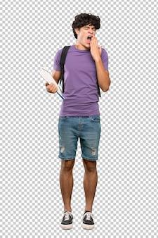 Uomo giovane studente che sbadiglia e che copre la bocca spalancata con la mano