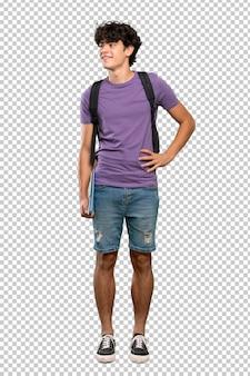 Uomo giovane studente in posa con le braccia all'anca e sorridente