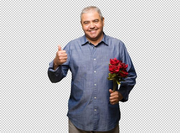 Uomo invecchiato centrale che celebra il giorno di biglietti di s. valentino che sorride e che solleva pollice in su