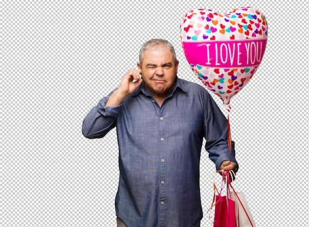 Uomo invecchiato centrale che celebra le orecchie della copertura del giorno di biglietti di s. valentino con le mani
