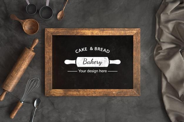 Utensilios de panadería de vista superior con maqueta de pizarra