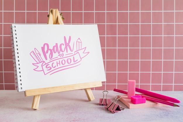 Útiles escolares con pintura de madera, caballete y lápices.