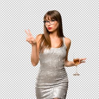Vacanze di natale. donna che indossa un abito di paillettes con champagne festeggia il nuovo anno