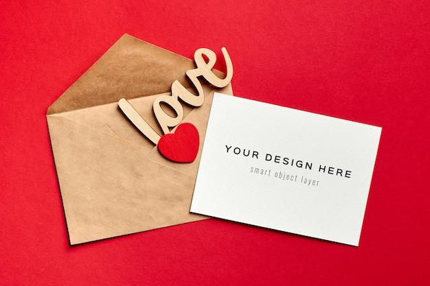 Valentijnsdag kaart mockup met envelop en houten decoraties liefde en hart op rood