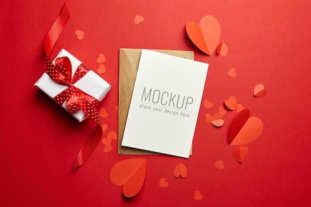 Valentijnsdag kaart mockup met envelop, geschenkdoos en rode papieren harten