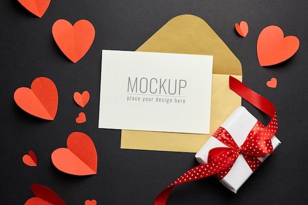 Valentijnsdag kaart mockup met envelop, rode harten en geschenkdoos op zwart papier