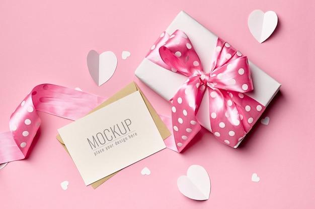 Valentijnsdag kaart mockup met geschenkdoos en papieren hartjes op roze