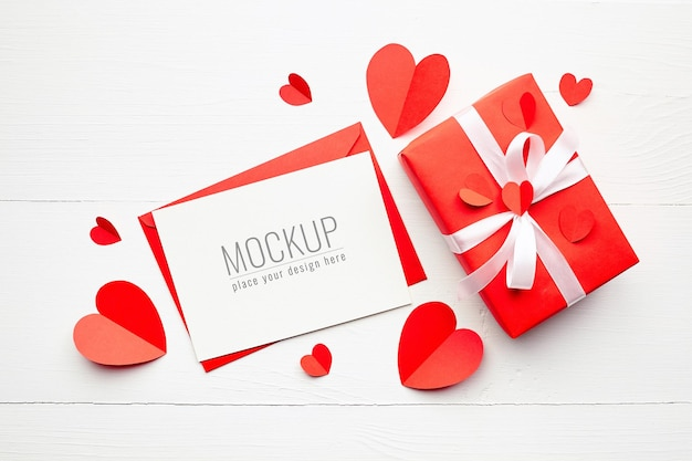 Valentijnsdag kaart mockup met geschenkdoos en rode papieren harten op witte ondergrond