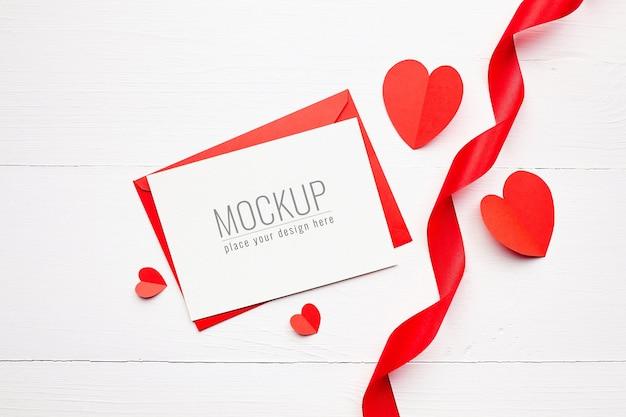 Valentijnsdag kaart mockup met geschenkdoos, rood lint en papieren hartjes op witte houten oppervlak