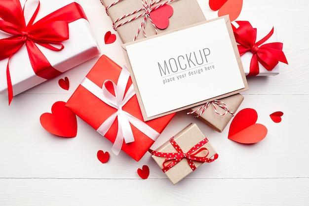 Valentijnsdag kaart mockup met geschenkdozen en rode papieren harten op witte ondergrond