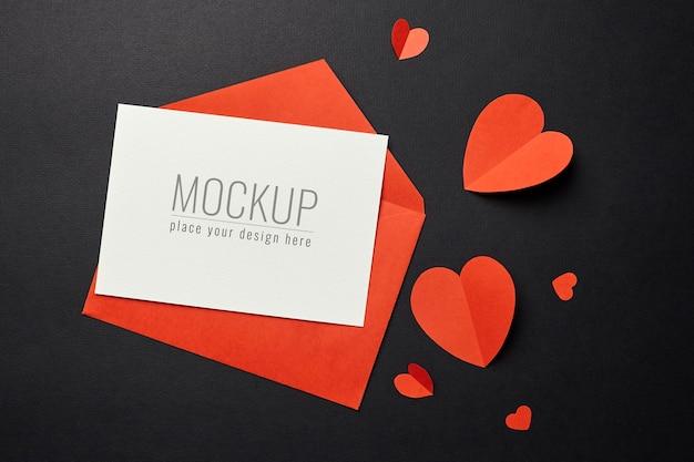 Valentijnsdag kaart mockup met rode envelop en harten op zwart papier