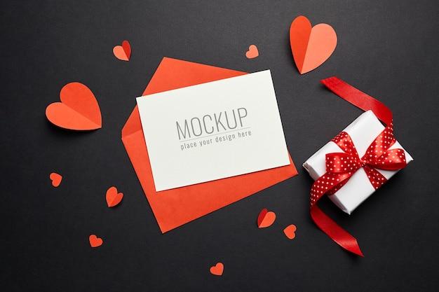 Valentijnsdag kaart mockup met rode envelop, harten en geschenkdoos op zwart papier