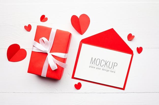 Valentijnsdag kaart mockup met rode geschenkdoos en harten op wit