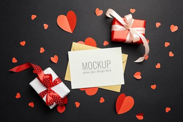 Valentijnsdag kaart mockup met rode papieren harten en geschenkdozen op zwarte ondergrond