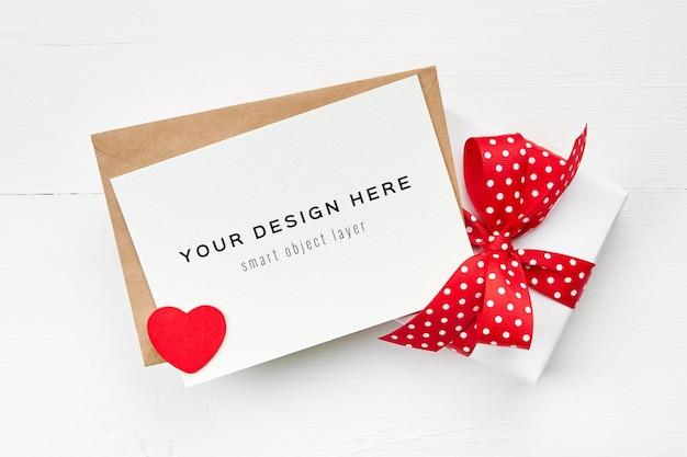 Valentijnsdag kaart mockup met rood hart en geschenkdoos met strik op wit