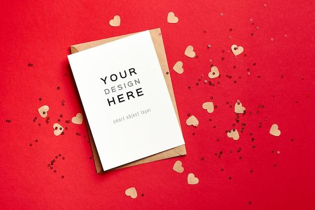 Valentijnsdag kaartmodel met envelop en kleine papieren harten op rood