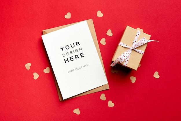 Valentijnsdag kaartmodel met geschenkdoos en kleine papieren hartjes op rood