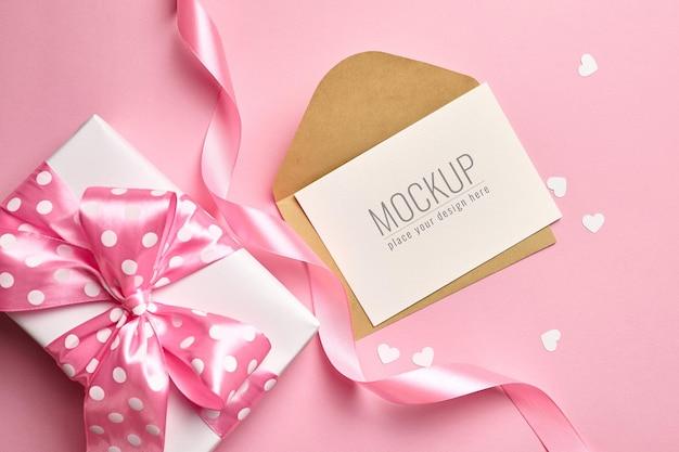 Valentijnsdag kaartmodel met geschenkdoos en kleine papieren hartjes op roze