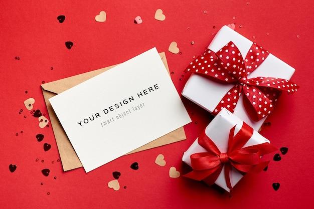 Valentijnsdag kaartmodel met geschenkdozen en kleine papieren hartjes op rood