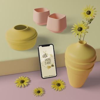 Vasi 3d con fiori accanto al cellulare con mock-up