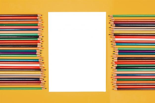 Vel papier met plaats voor tekst op een gele achtergrond, een set kleurpotloden, mockup, scene maker